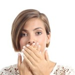 Woman covering her mouth because bad breath isolated on a white background