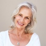 Close up portrait of beautiful older woman smiling and standing by wall