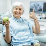 Portrait of a beautiful senior woman with healthy smile holding green apple at the dental office