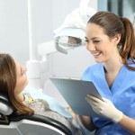 Dentist holding a medical history asking information to a patient before treatment sitting on a chair in a clinic box