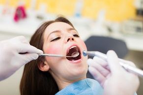 Dentist doing a dental treatment on a female patient