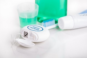 Dental floss focused with  toothbrush, toothpaste, mouthwash, at background, essential oral care products recommended by dentist.