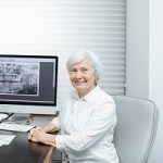 Portrait of a smiling senior woman sitting in the doctor's office with dental x-ray on the background